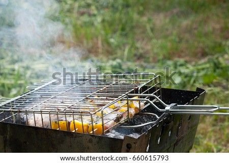 fish with vegetables and sweet pepper prepared on the grill grate in the iron grill in the garden during the summer sunny day #660615793