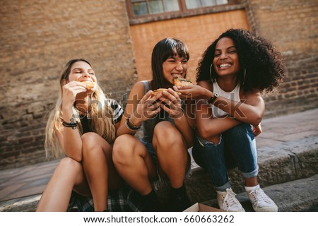 Picture of female friends sitting outdoors and eating pizza. Three young women sitting on the sidewalk and having pizza. #660663262