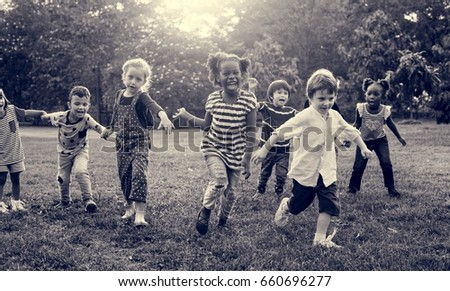Group of kindergarten kids friends playing playground fun and smiling #660696277