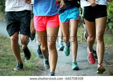 A cross country team runs a workout in a group in a park outside. #660708508