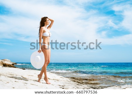 Beautiful woman in white bikini. Young and sporty girl posing on a beach at summer. #660797536