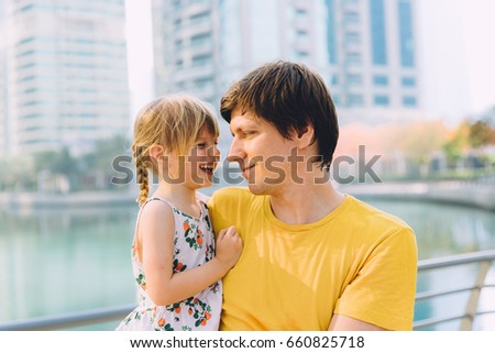 Close up portrait of father with his little daughter outdoors in the city #660825718