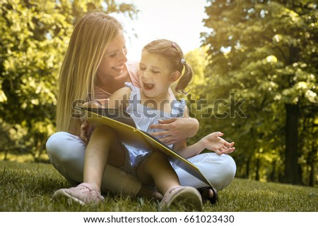 Mother and daughter sitting on green grass and reading book together. Little girl sitting on mother lap. #661023430