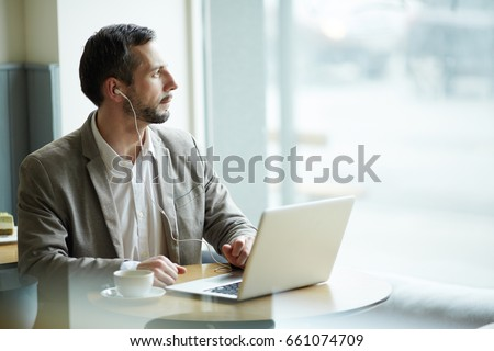 Portrait of mature pensive man looking away to window while using laptop in cafe, with earphones #661074709