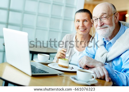 Happy seniors spending time by cup of tea with dessert in cafe #661076323
