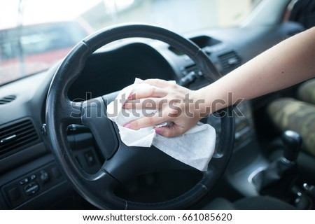 Young woman hands cleaning the interior of car by white rag / clothes #661085620