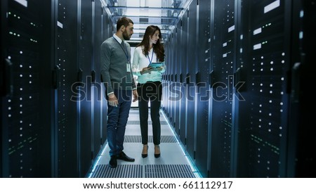 Female and Male IT Engineers Discussing Technical Details in a Working Data Center/ Server Room. Royalty-Free Stock Photo #661112917