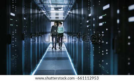 Female IT Technician and Male Server Engineer Talk and Discuss. They are in Working Data Center full of Rack Servers. Woman Holds Laptop. #661112953