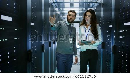 IT Engineer Shows Working Data Center / Server Room to Female Chief Engineer who Holds Tablet Computer. Royalty-Free Stock Photo #661112956