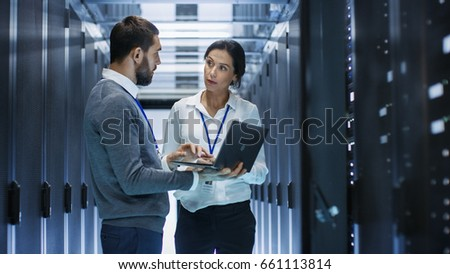 Male IT Specialist Holds Laptop and Discusses Work with Female Server Technician. They're Standing in Data Center, Rack Server Cabinet is Open. Royalty-Free Stock Photo #661113814