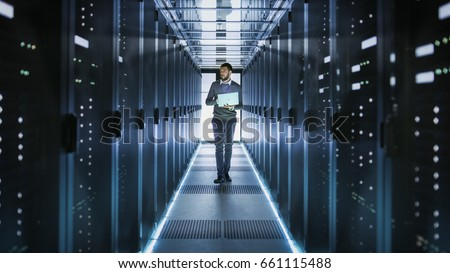IT Technician Works on Laptop in Big Data Center full of Rack Servers. He Runs Diagnostics and Maintenance, Sets System Up. #661115488