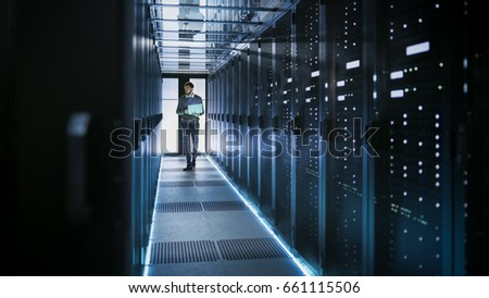IT Technician Works on Laptop in Big Data Center full of Rack Servers. He Runs Diagnostics and Maintenance, Sets System Up. #661115506