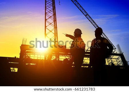Silhouette Teams Businessman engineer looking blueprint in a building site over Blurred construction site at sunset #661231783