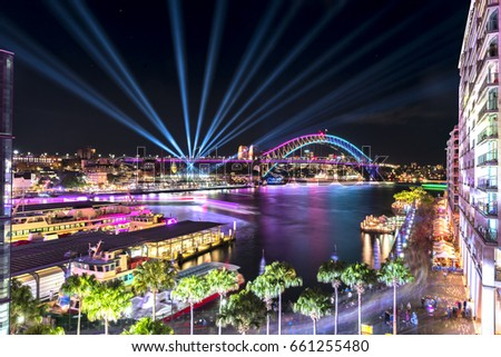 Circular Quay and Sydney Harbour Bridge illuminated with colorful light, during the Vivid Sydney 2017  Royalty-Free Stock Photo #661255480