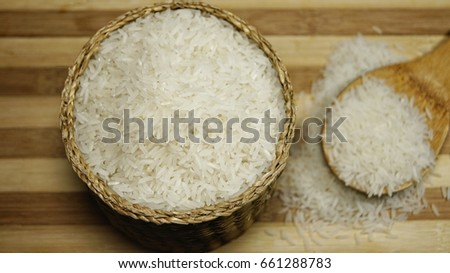 Raw rice in a wicker basket and bamboo scoop on wooden board. Selective focus image. #661288783
