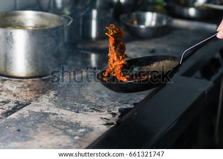 Chef is stirring vegetables in wok #661321747