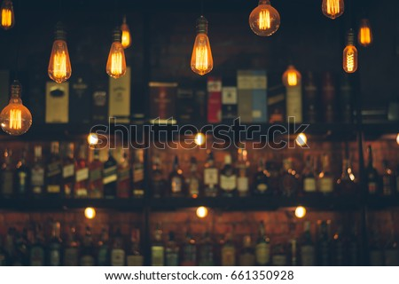 Soft focus picture of vintage lamps with blurred liquor bar in Vintage photo filter style. Royalty-Free Stock Photo #661350928