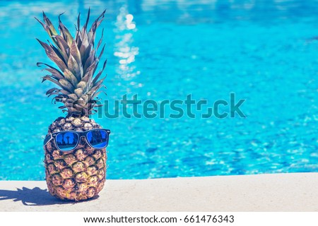 Funny pineapple in sunglasses near swimming pool. Royalty-Free Stock Photo #661476343