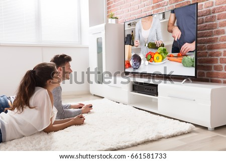 Happy Young Couple Sitting On Sofa Watching Recipe On Television At Home #661581733