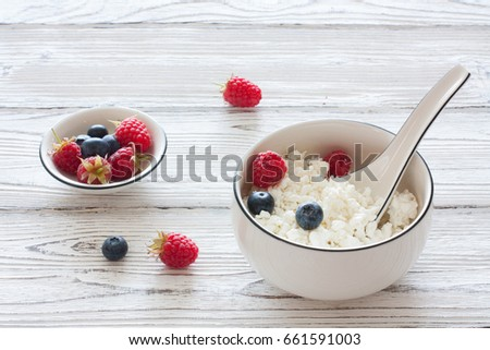 Homemade cottage cheese with fresh berries in white ceramic plate over old white wood background #661591003