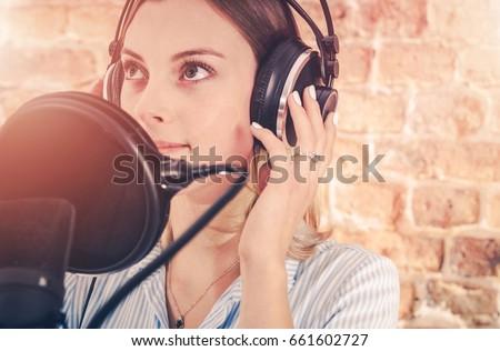 Caucasian Girl in Her 20s in the Audio Recording Studio. Recording Voice.
