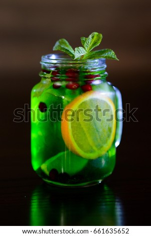 refreshing cocktail with lime, lemon and mint on black background