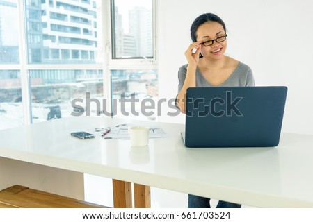 Woman sitting at desk, indoors by window, day, using laptop. asian, long hair, adult #661703524