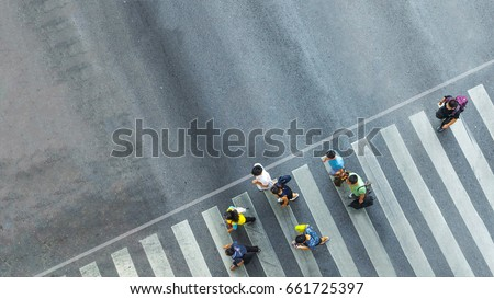 the busy city crowd move to pedestrian crosswalk on business traffic road (Aerial photo, top view) #661725397