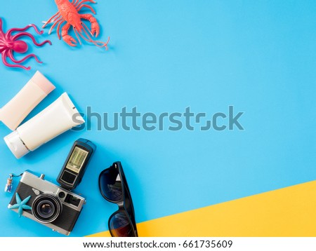Summer Background, Summer holiday concept, Travel Concept with Untidy props are Sunscreen, Glasses, Camera, sea animal and hat on blue and yellow background. #661735609