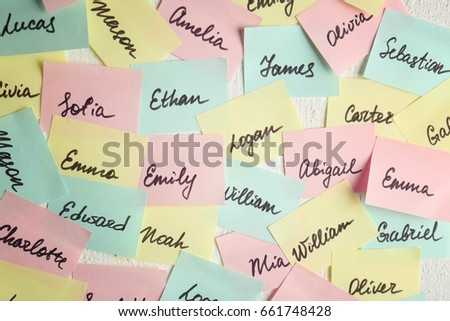 Closeup of paper stickers with different names on white wall. Concept of choosing baby name Royalty-Free Stock Photo #661748428