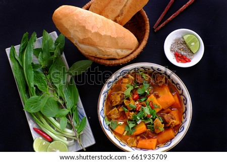 Vietnam food, bread with stewed beef, a popular meal at morning, eat attach parsley, basil, lemon pepper and salt make so delicious taste Royalty-Free Stock Photo #661935709