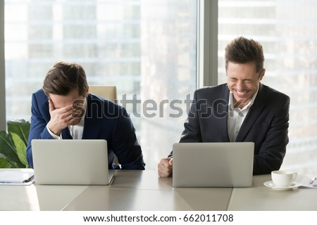 Two businessmen laughing out loud at workplace, office workers screaming with laughter and can not stop, funny positive emotions at work, cheerful colleagues having fun sitting at desk with laptops Royalty-Free Stock Photo #662011708