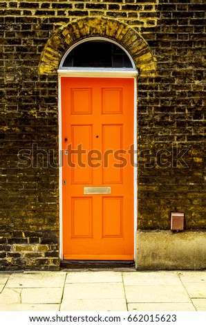 stylish entrance to a residential building, an interesting facade of the old brick arches above the door, a typical old English buildings, london #662015623