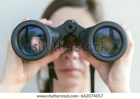 Girl looking through the binoculars. Find and search concept. Royalty-Free Stock Photo #662074057