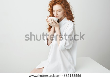 Beautiful redhead girl with curly hair smiling holding cup sitting on table over white background. Closed eyes. #662133556