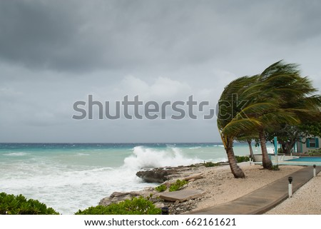 A hurricane is about to batter this caribbean beach hut. The seas are raging and the skies show the tropical storm as the power of nature is demonstrated. Waves crash on the shore #662161621