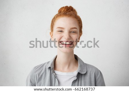 People, youth, happiness concept. Delightful redhead female with beautiful freckled face casually dressed smiling and looking directly in camera standing isolated against blank studio wall background #662168737