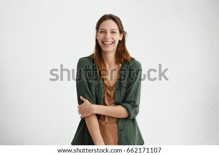 People, beauty and lifestyle concept. Shot of attractive sensual woman with wide smile dressed in green jacket and brown T-shirt smiling broadly being happy to meet her best friend. Joyful nice female #662171107