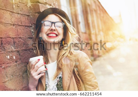 Cheerful woman in the street drinking morning coffee in sunshine light #662211454