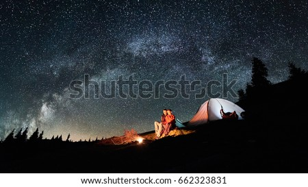 Night camping. Romantic couple tourists have a rest at a campfire near illuminated tent under amazing night sky full of stars and milky way. Astrophotography. Picture aspect ratio 16:9