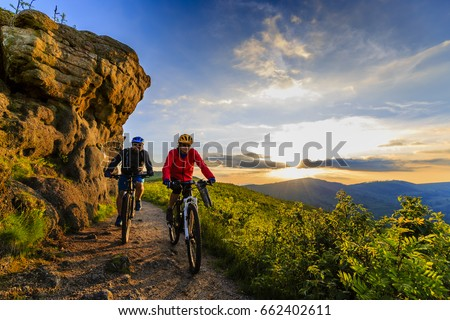 Mountain biking women and man riding on bikes at sunset mountains forest landscape. Couple cycling MTB enduro flow trail track. Outdoor sport activity. Royalty-Free Stock Photo #662402611