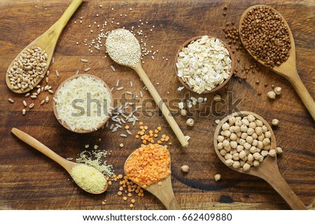 Different types of cereals in wooden spoons - buckwheat, chickpeas, rice, quinoa, lentils #662409880