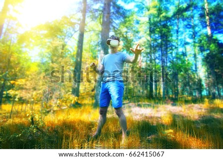man in a VR glasses operating in virtual reality forest. Technology concept #662415067