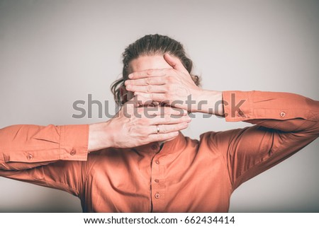 handsome man covered face with hands, studio shot isolated on the background #662434414