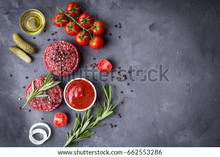 Ground raw meat patties with seasonings, onion, tomatoes, pickles, ketchup, olive oil. Meat patties ready to cook. Barbecue party. Space for text. Background. Patties to be grilled/roasted/fried #662553286