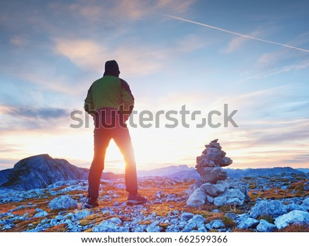 Tourist guide at stocked stones on Alps peak. Strong hiker enjoy sunset in   Alpine mountain. Alone man on few days trek