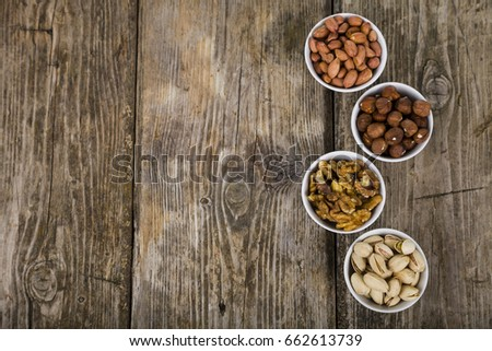 Four bowls with nuts on a  wooden table. Different kinds of tasty and healthy nuts. Top view #662613739
