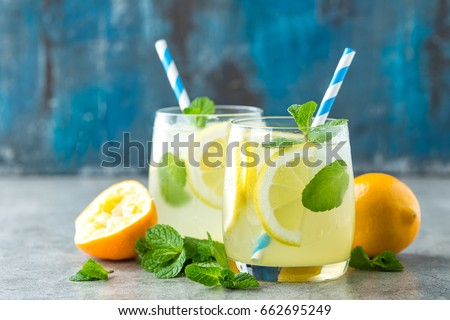 Lemonade or mojito cocktail with lemon and mint, cold refreshing drink or beverage with ice Royalty-Free Stock Photo #662695249