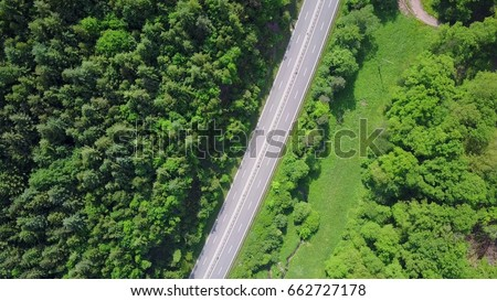 country road through forest in Germany, 150 meters above ground level, green forest and two lane road during summer time #662727178