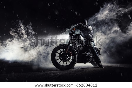 High power motorcycle chopper with man rider at night. Fog with backlights on background. #662804812